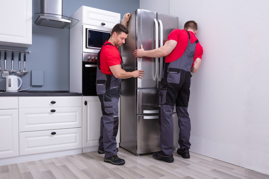 Two Young Male Movers Placing a stainless Steel Refrigerator In Kitchen remodel