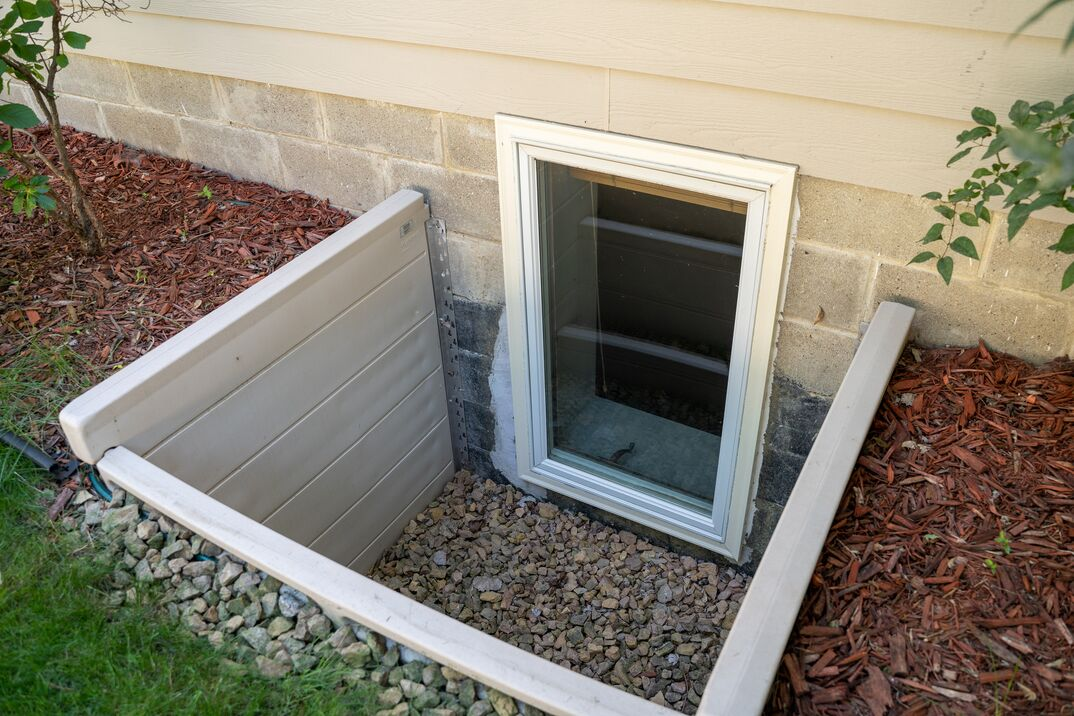 Exterior view of an egress window in a basement bedroom  These windows are required as part of the USA fire code for basement bedrooms