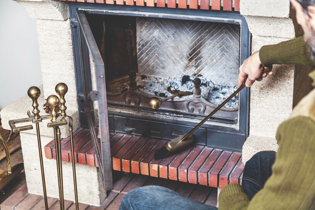 man cleans the furnace of fire with a spatula and brush on a long handle