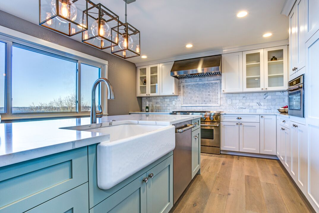 Beautiful kitchen room with green island and farm sink