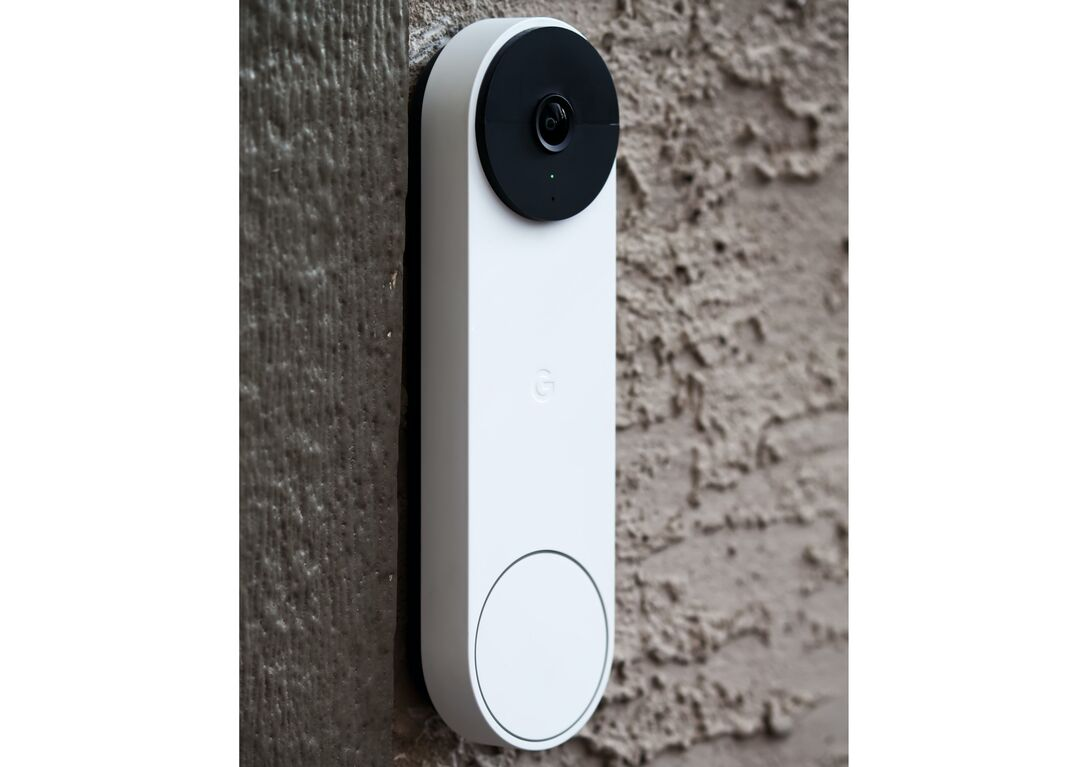 A white Google Nest Doorbell video security device with a black circular camera is affixed to a brown stucco exterior wall.