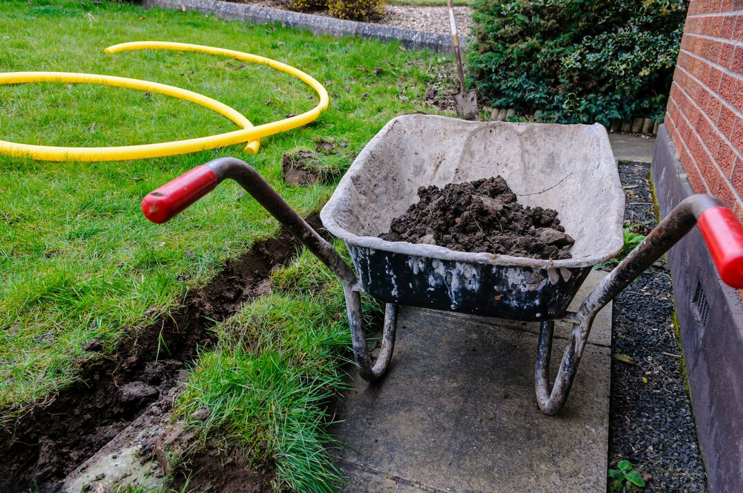wheelbarrow full of dirt from digging a trench for a french drain