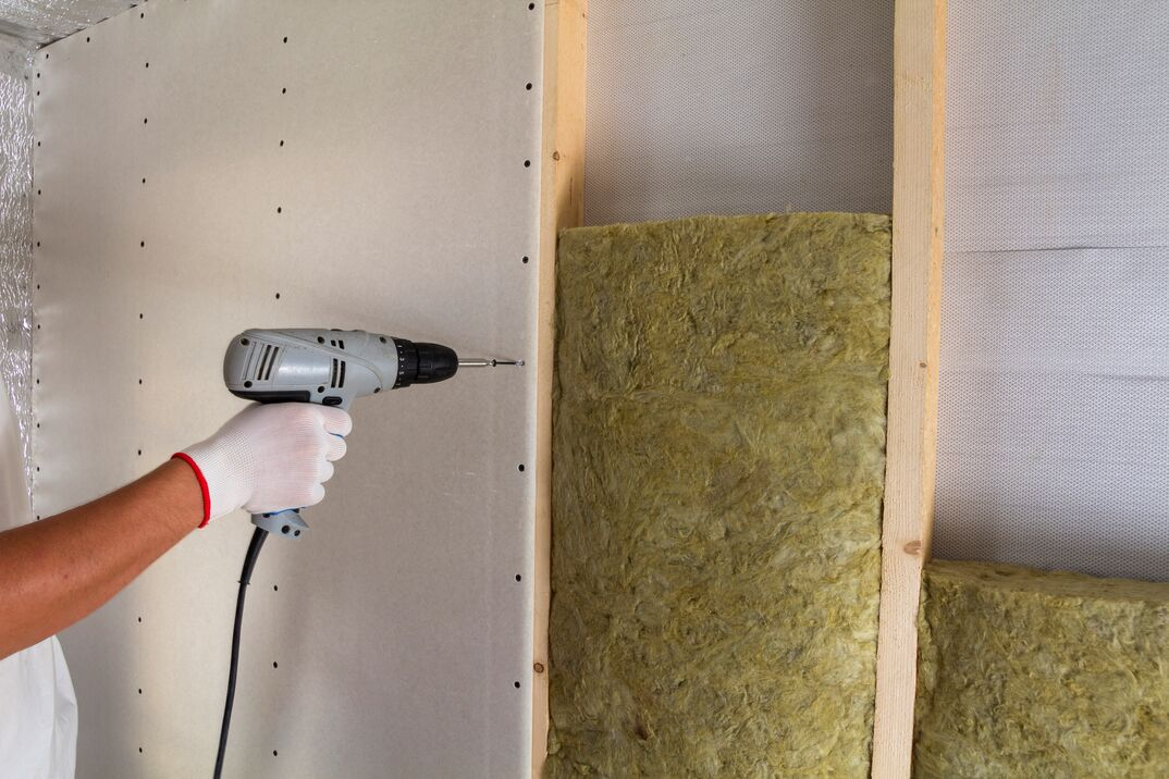 Close-up of worker hand with electric screwdriver fastening drywall to wooden timber frame with insulation mineral rock wool staff. Warm home, construction and renovation concept., low energy bills