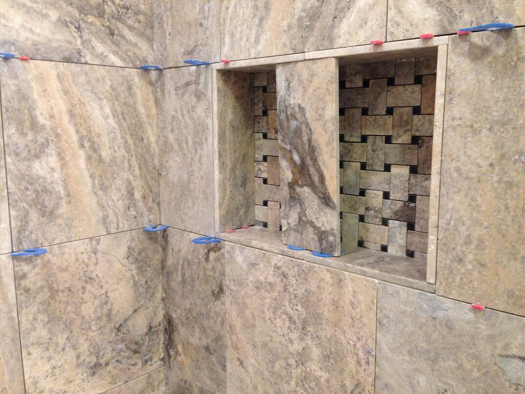 shower with travertine stone tile being installed