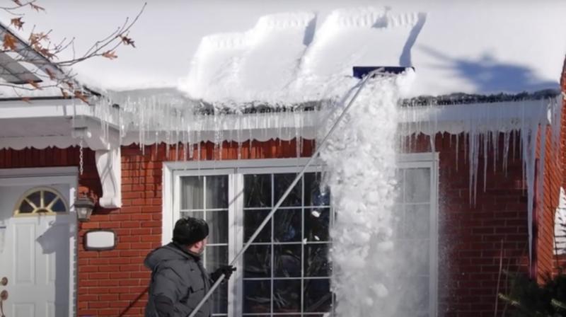 man raking snow from roof