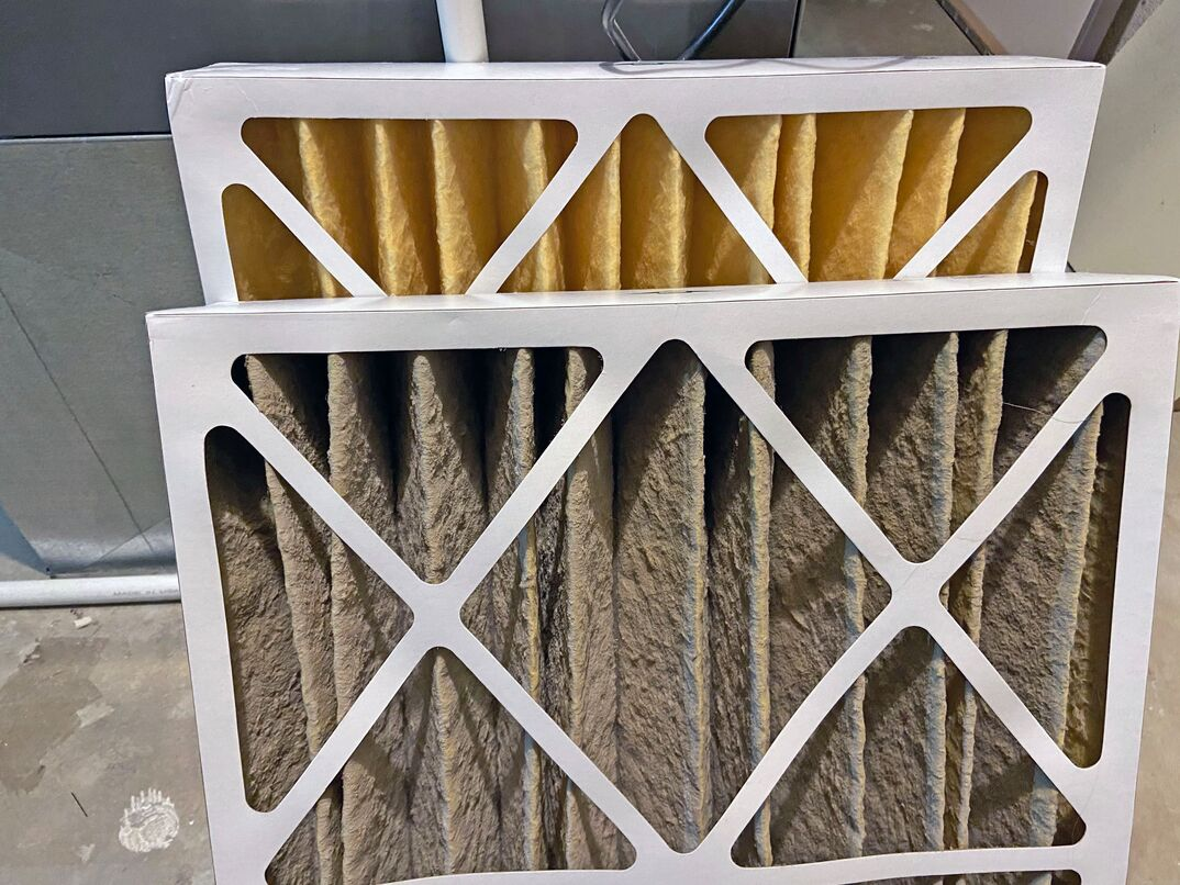 A side by side comparison of a clean HVAC furnace filter and a dirty filter