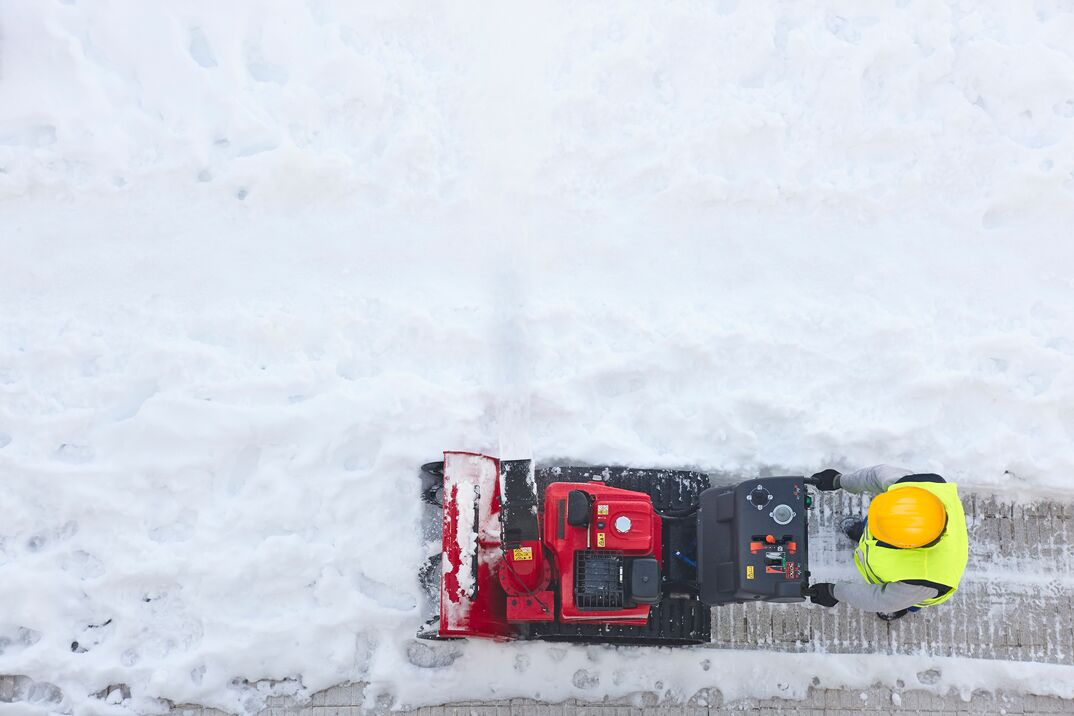 Worker cleaning snow on the sidewalk with a snowblower. Wintertime