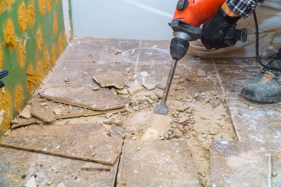 Worker remove, demolish old tiles a bathroom with jackhammer