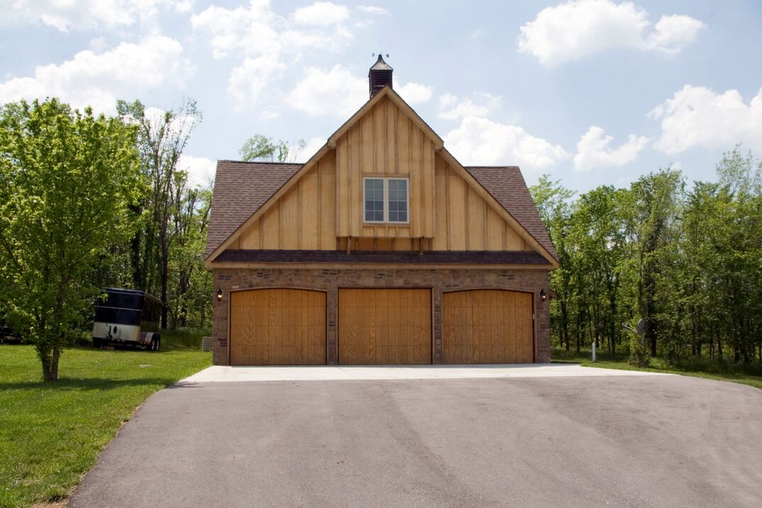 Detached residential three-car garage with a wood and stone exterior