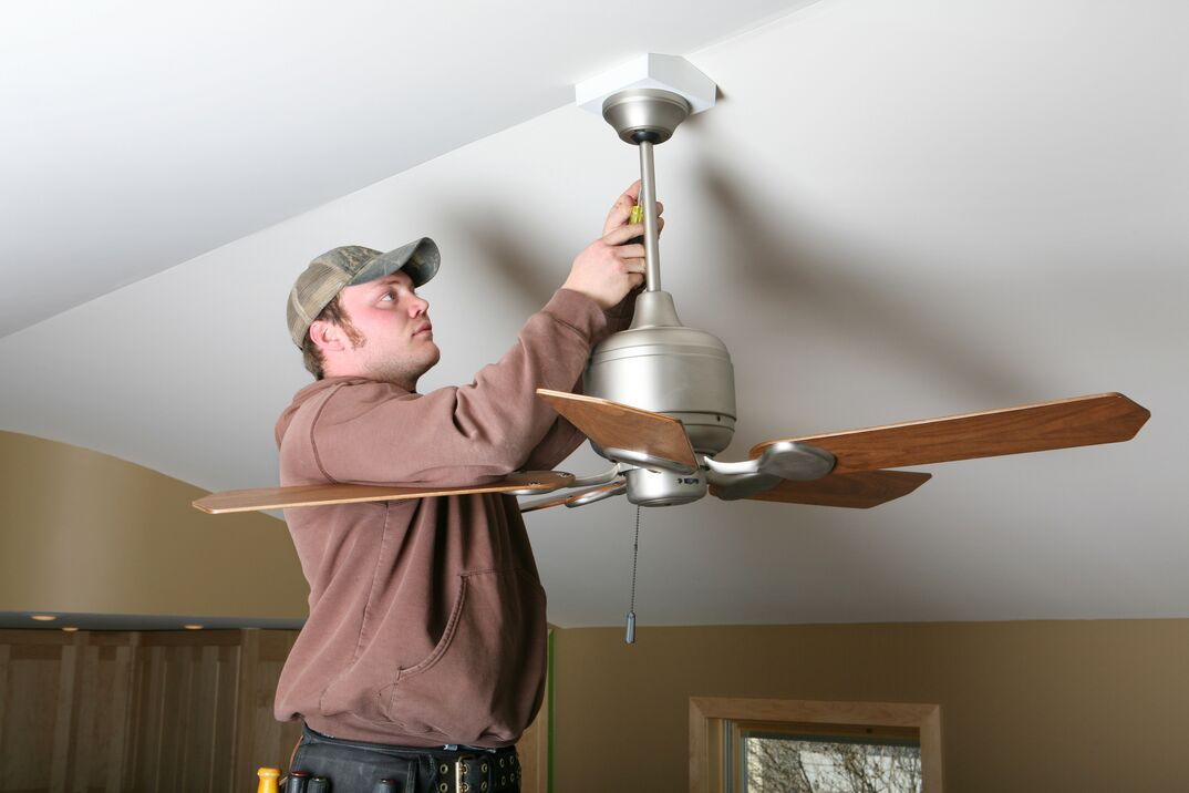 an electrician works to install a ceiling fan with a downrod
