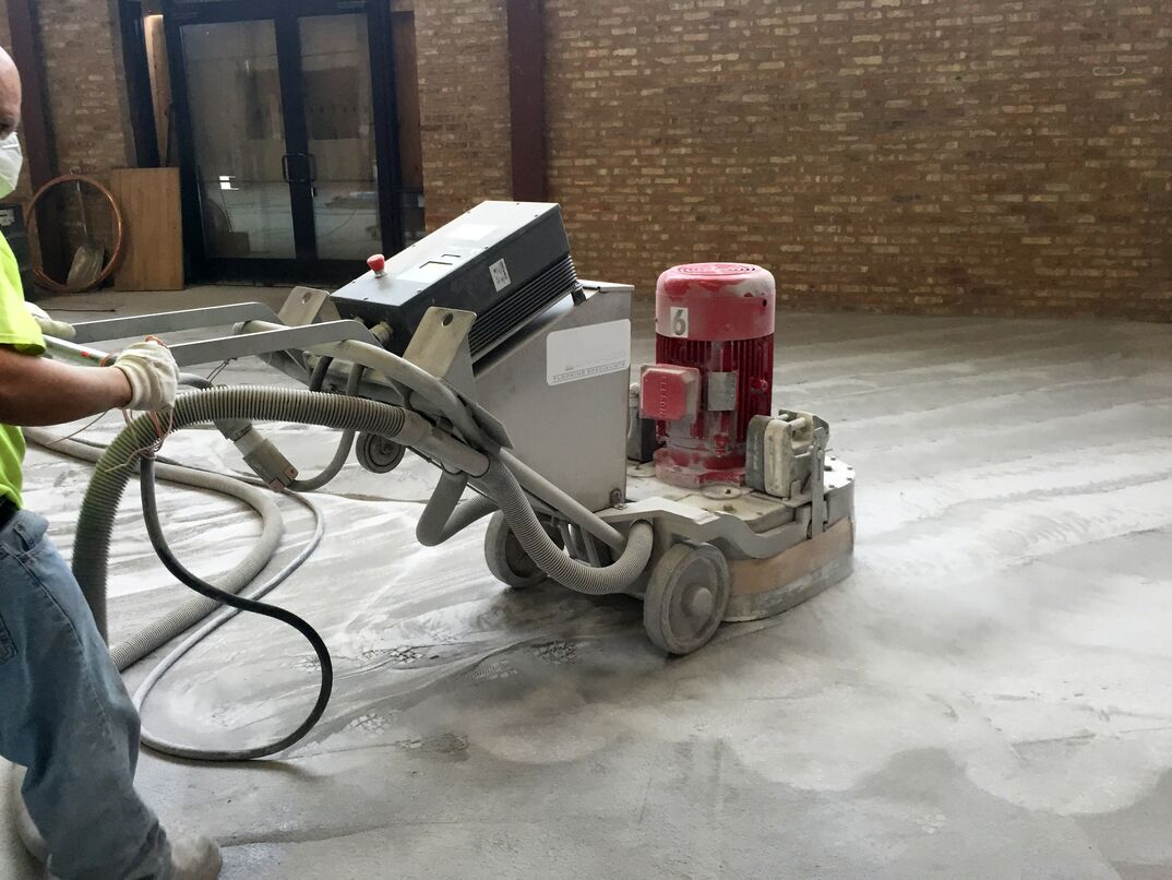 A contractor weilds a large floor grinding  polishing machine to sand down a new Terrazo floor