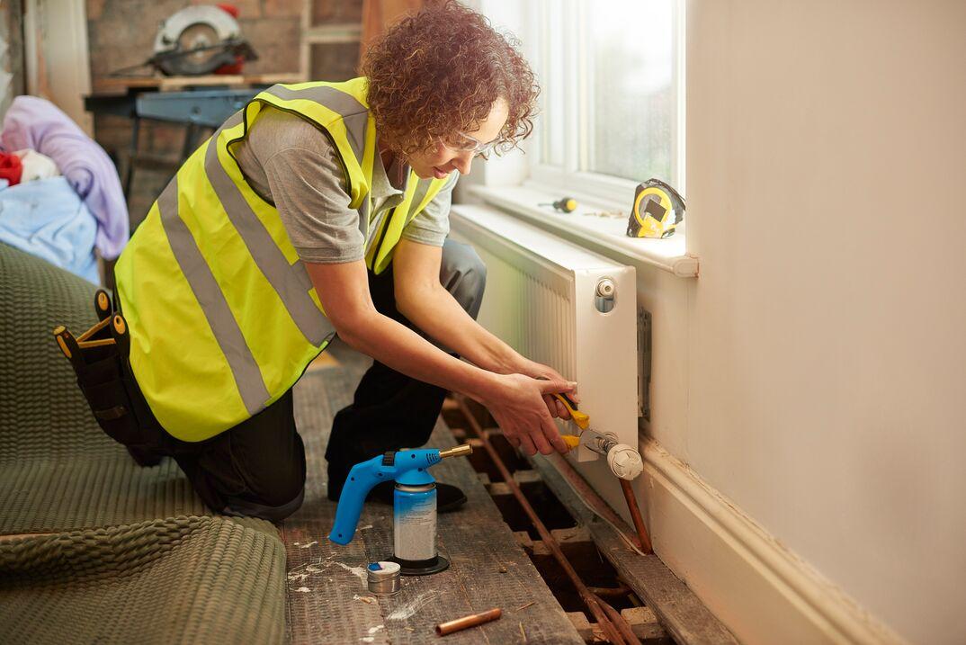 female contractor repairs heater