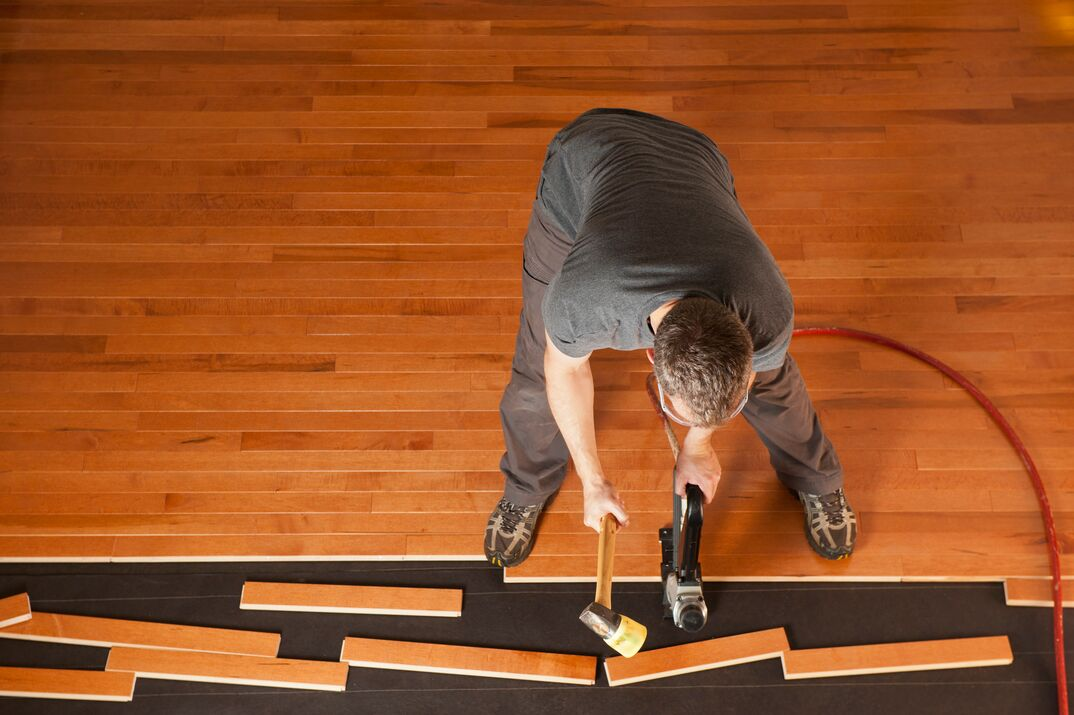 Man installing a wood floor shown from above