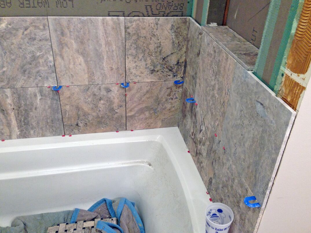 bathtub with travertine stone tile being installed
