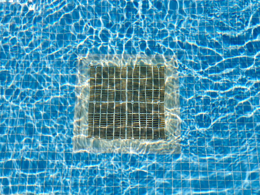 Pulsating blue pool water with reflections of the sun Drain grate for water at the bottom of the pool