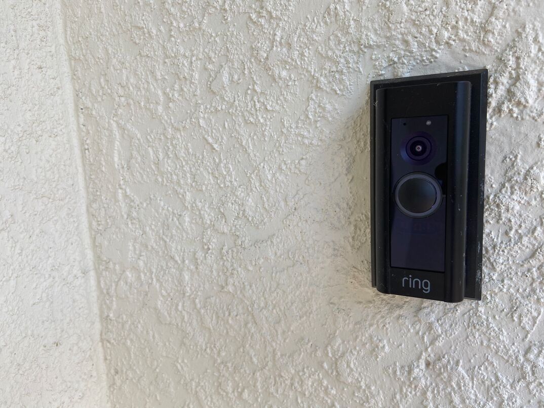 a black ring video camera mounted to a stucco wall