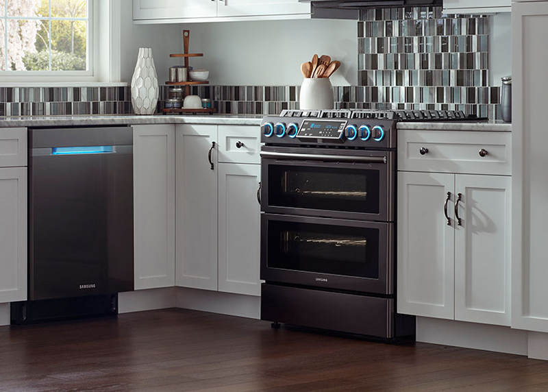 Modern kitchen featuring a Samsung smart stainless steel range with glowing blue knobs, a brown wood floor, a stainless steel dishwasher, a tile backsplash and a window with natural light coming in., white cabinetry