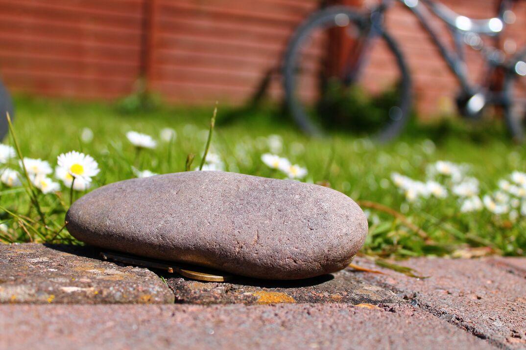 Hidden house key under a gray stone