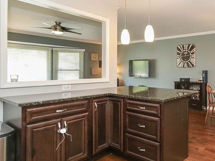 Kitchen island in a modern farmhouse home with a black granite top that includes a breakfast bar