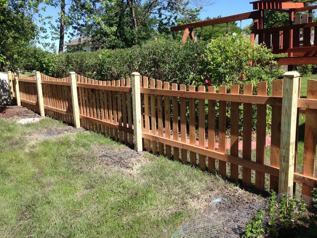 a newly installed cedar picket fence