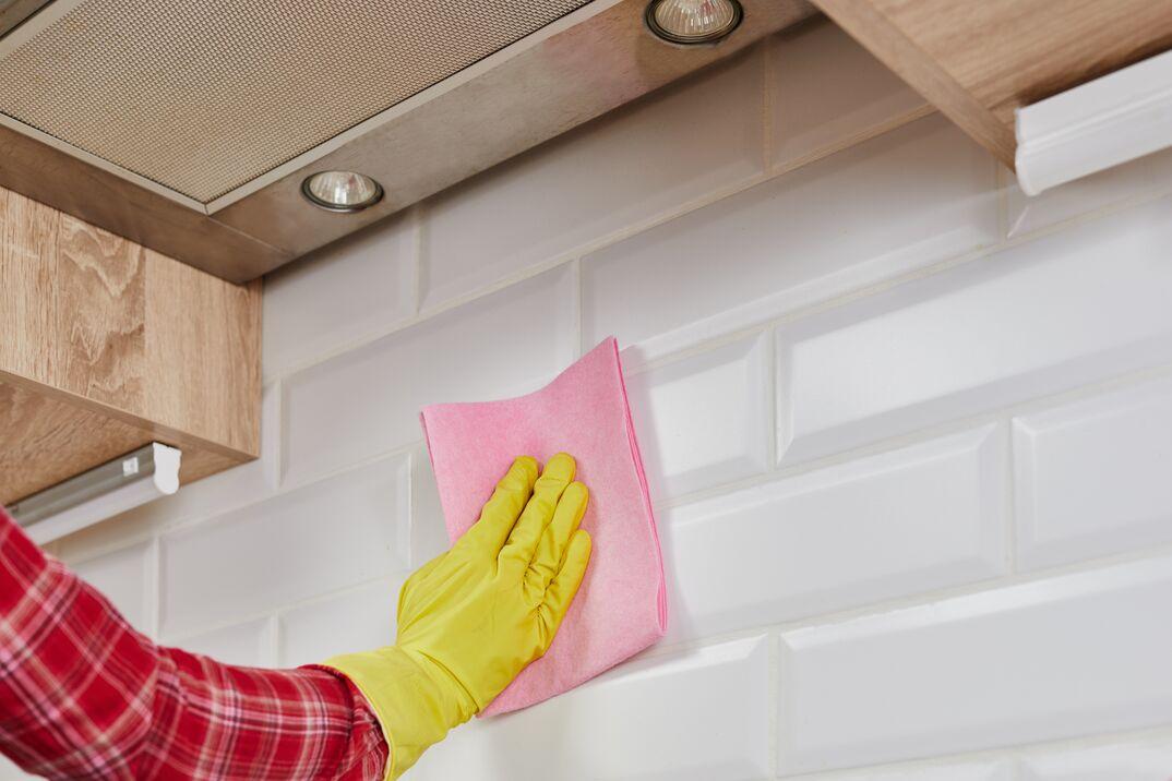 Person cleaning kitchen backsplash