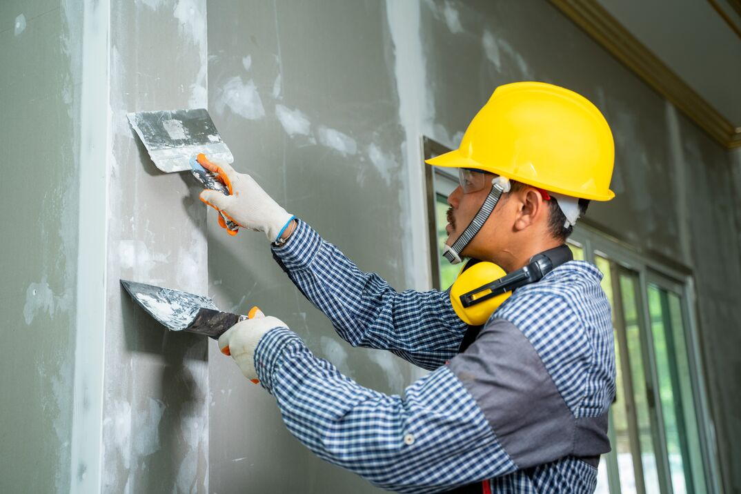 Construction industry worker using a putty knife and leveling in house under reconstruction
