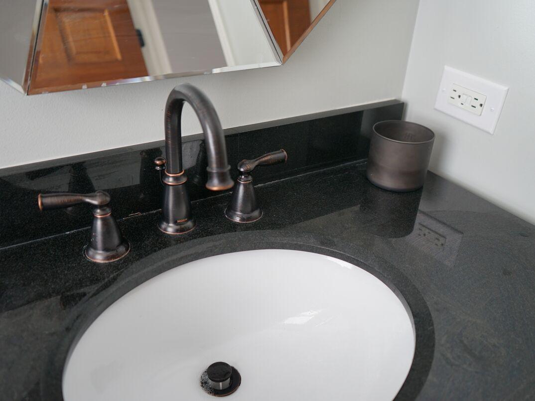 residential bathroom sink sits on a black granite countertop