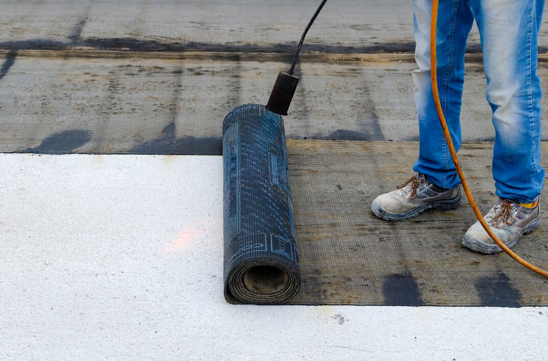 Roofer installing rolls of bituminous waterproofing membrane for the waterproofing of a terrace