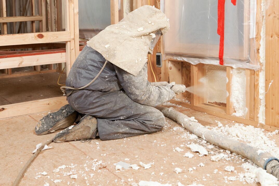 Worker in protective gear is Spraying Expandable Foam Insulation between Wall Studs