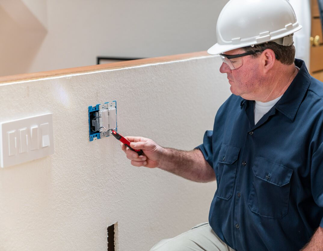 in a blue shirt and hard hat, Electrician, using a voltage detector before installing an outlet