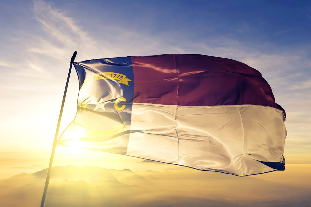 North Carolina state of United States flag textile cloth fabric waving on the top sunrise mist fog