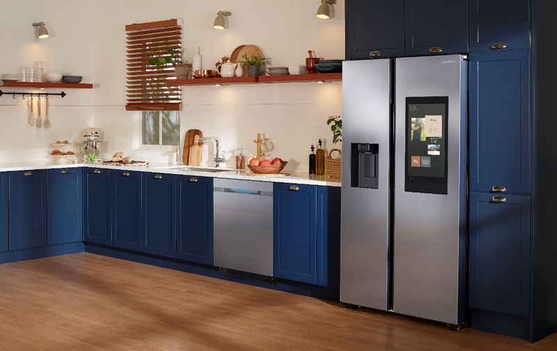 A stainless steel Samsung Smart refrigerator with a large digital display panel in a modern kitchen with brown wood floors and blue cabinets.