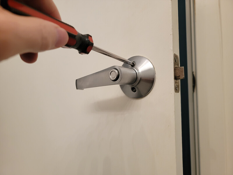 removing a doorknob with a screwdriver
