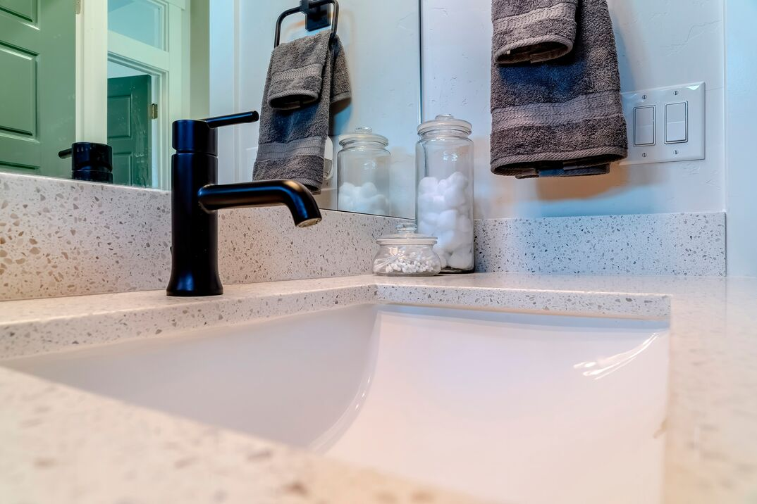 Closeup view from a side angle of a white undermount sink in a bathroom with granite white countertops  also visible are a dark-colored faucet