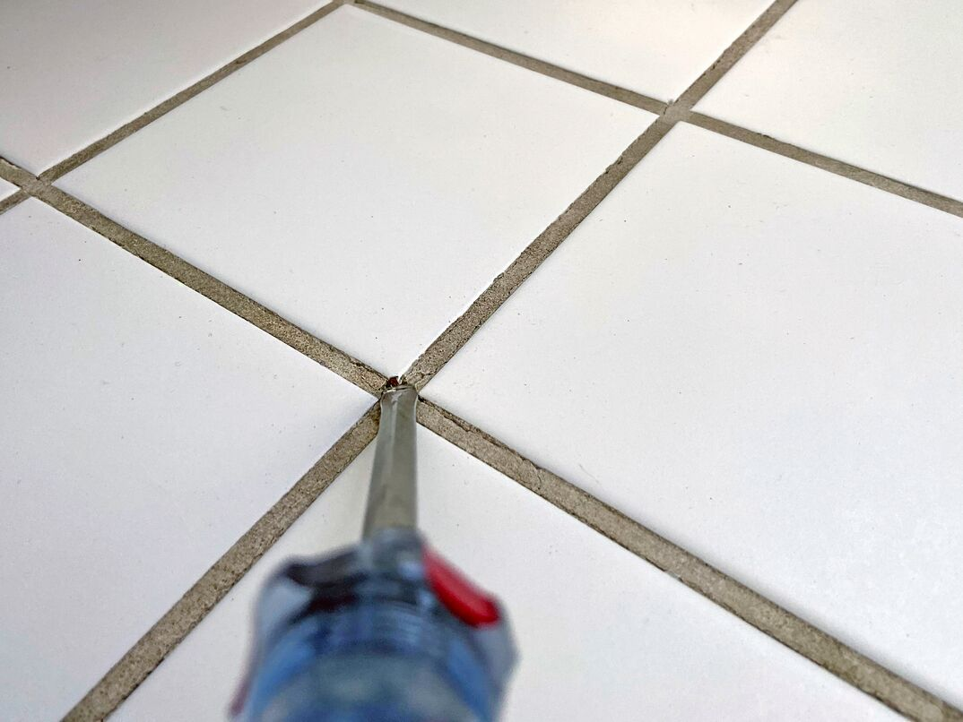 close up of a flathead screwdriver being used to chisel away broken grout from bathroom tile