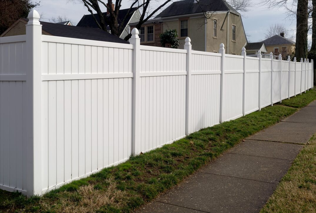 a wide shot of a White Vinyl Fence in a residential neighborhood