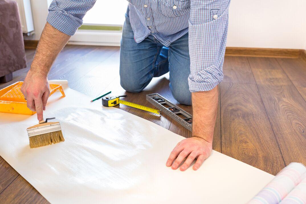 Handyman measuring wallpaper to cut