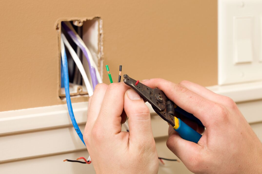 Worker Stripping Wire for Ceiling Speaker Control