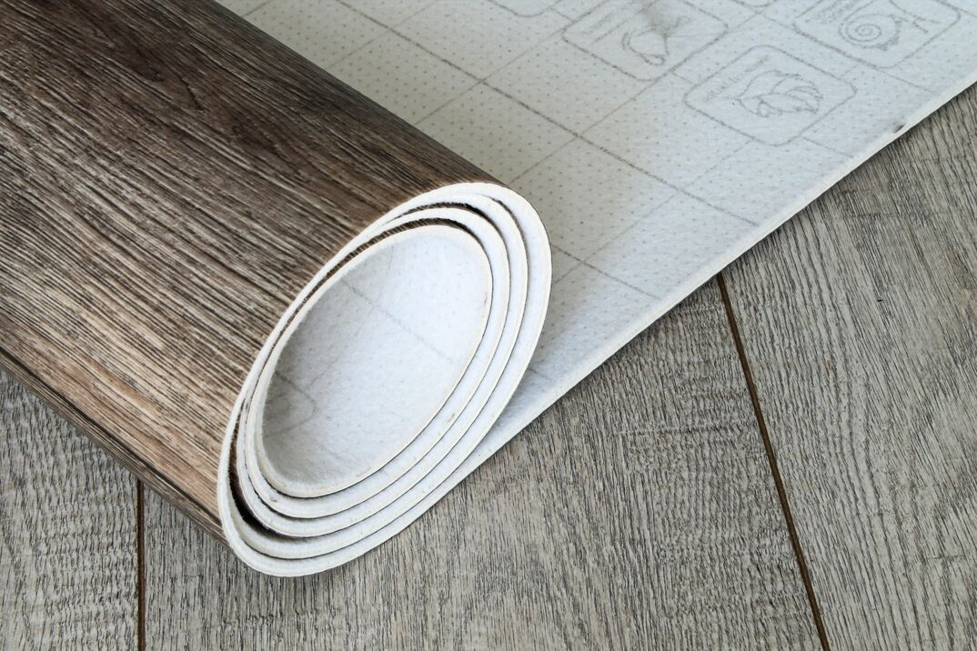 A roll of simulated wood vinyl tile is unrolled across a finished floor