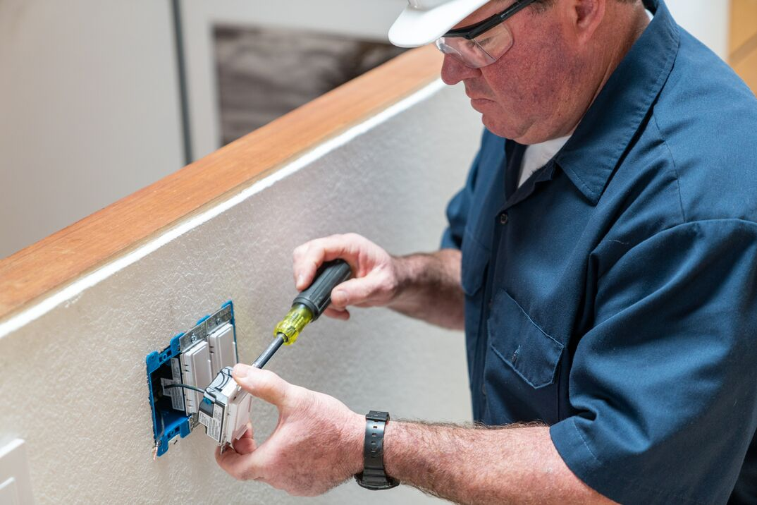 Electrician, in a blue shirt and hard hat, using an unsulated screwdriver to install a dimmer switch