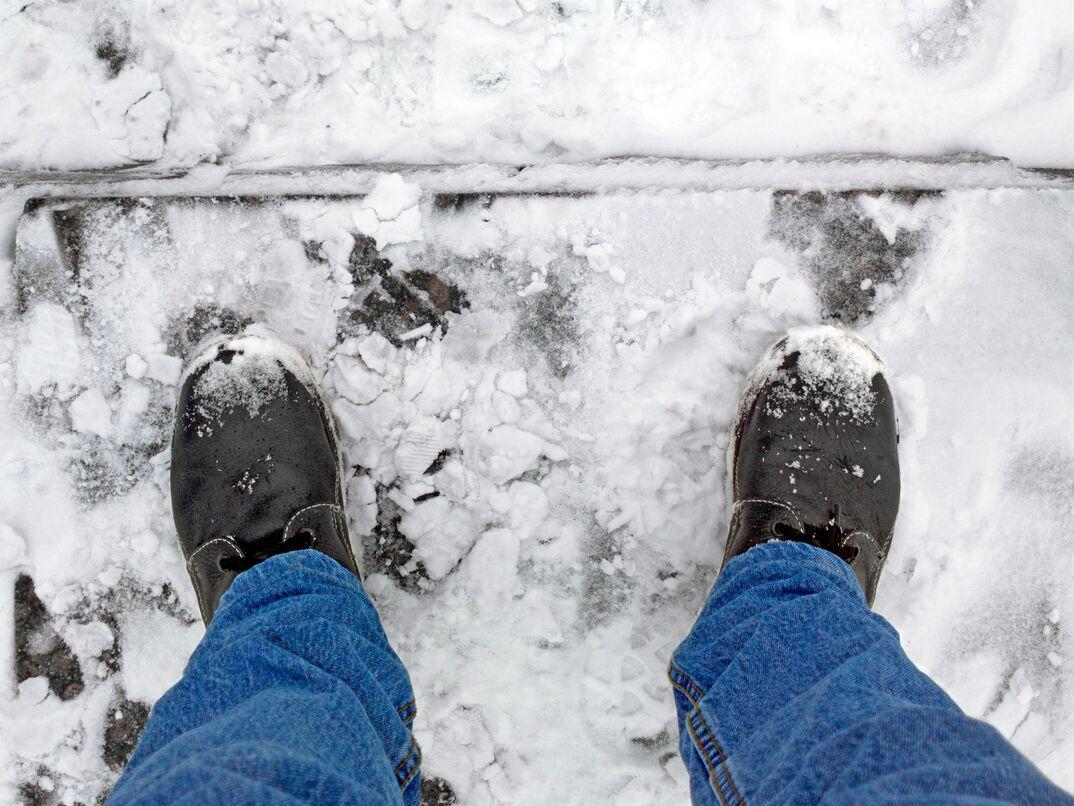 Man s boots on frozen concrete steps