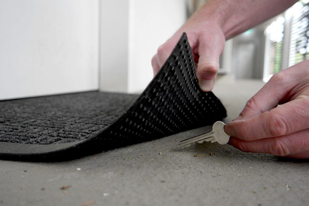 Man lifting edge of a door mat to pick up a key hidden underneath
