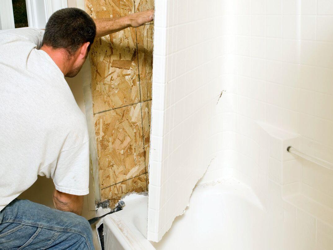 Construction Worker Removing a Fiberglass Bathtub