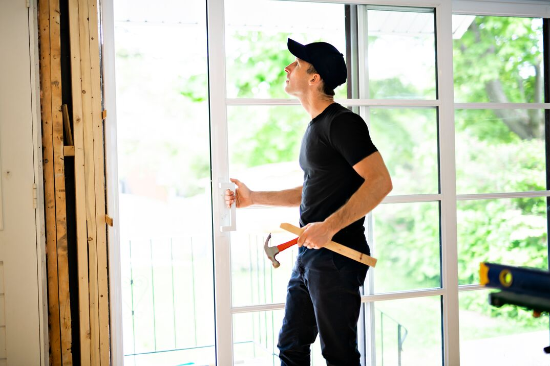 A handsome young man installing Double Sliding Patio Door in a new house construction site