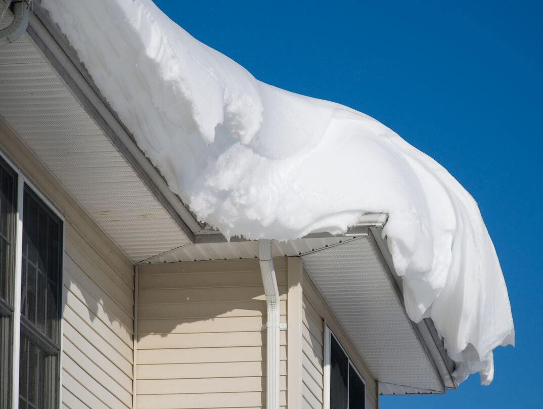 a beige residential home covered with a massive amount of snow on a clear day
