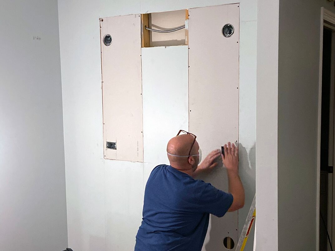 tradesman uses drywall mud or plaster and drywall tape to repair the drywall cuts required by the new electrical work