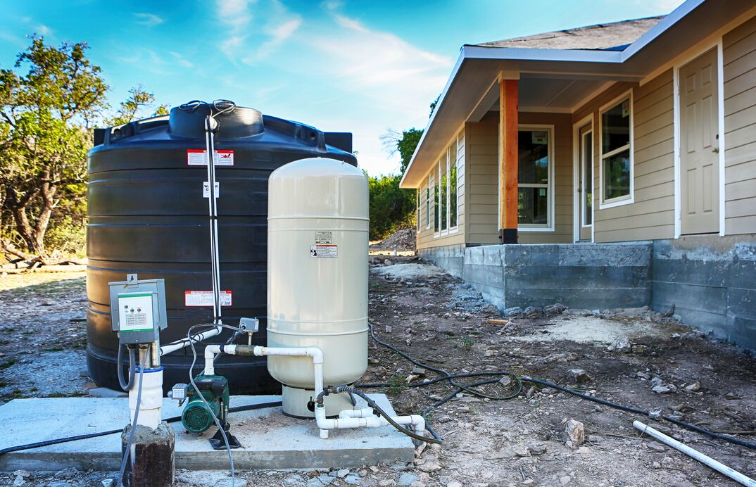 Deep water well set up in front of home construction