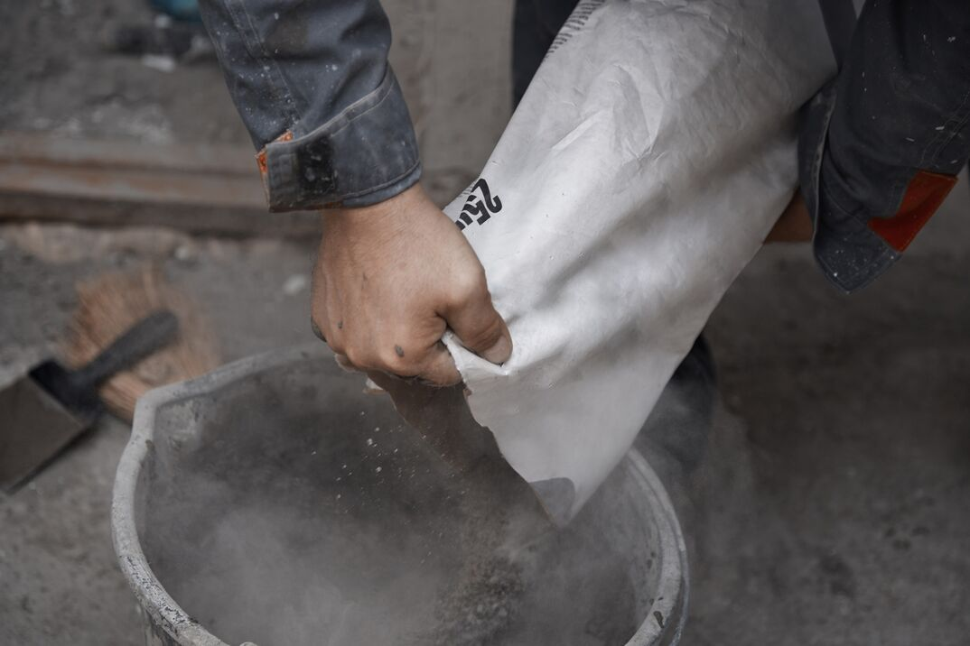 Construction worker pouring the cement to the bucket