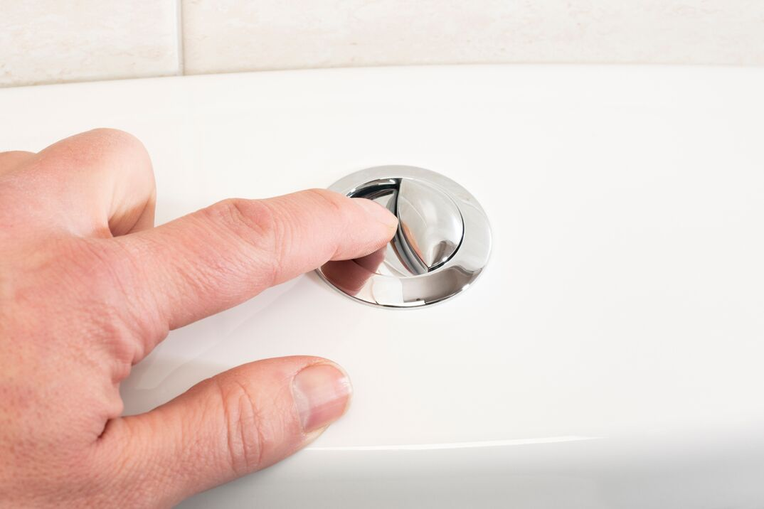 finger pressing toilet flush