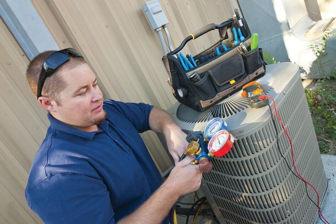 technician checking external HVAC unit
